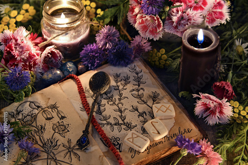 Still life with old book with botanical drawings, black candles, flowers and ritual objects. Mystic background with ritual esoteric objects, occult, fortune telling and halloween concept
