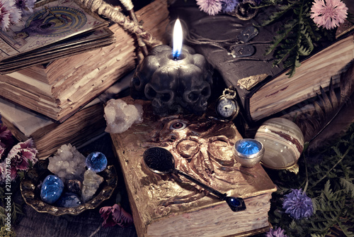 Still life with scary skull black candle, witch book and ritual objects in mystic light. Mystic background with ritual esoteric objects, occult, fortune telling and halloween concept
