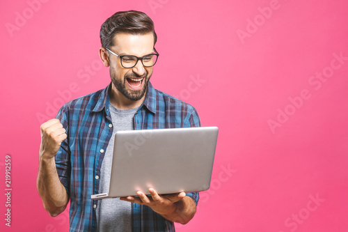 Fotomural I'm a winner! Happy man holding laptop and celebrating his success over pink background