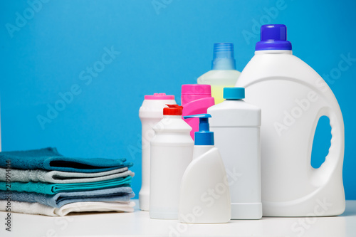 Obraz Photo of different bottles of cleaning products and colored towels isolated on blue background - fototapety do salonu