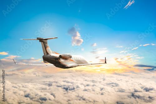 Fotografie, Obraz  Jet plane flying high up over clouds into sunset