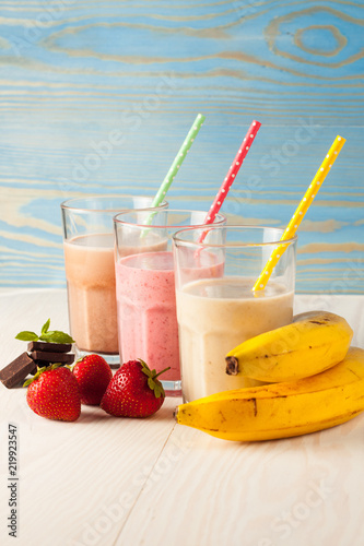 Poster Cuisine Long glasses of milkshakes with chocolate, strawberry, banana, with ice cream on white and blue background. Shakes and smoothies. Milk shake and cocktail for summer.