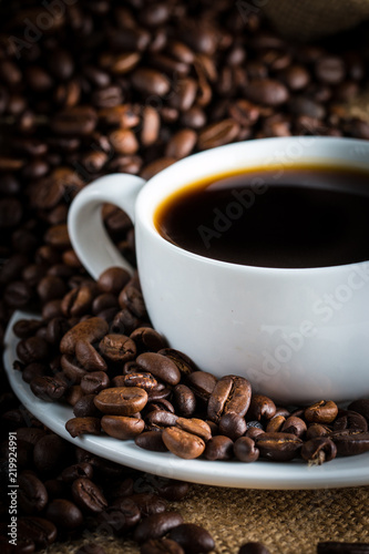 Deurstickers koffiebar Coffee cup and beans on a rustic background. Coffee Espresso and a piece of cake with a curl. Cup of Coffee and coffee beans on table.