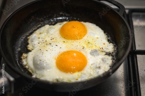 Foto op Plexiglas Gebakken Eieren two eggs cooked in a black cast iron skillet