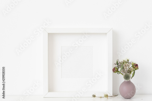 6ab42ef5c1ef White square portrait frame mockup with dried field wild flowers in vase on  white wall background. Empty frame
