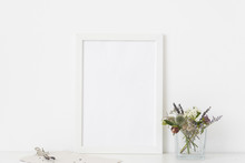 White A4 Portrait Frame Mockup With Small Bouquet Of Dried Flowers In Transparent Vase And Clamp On White Wall Background. Empty Frame, Poster Mock Up For Presentation Design.
