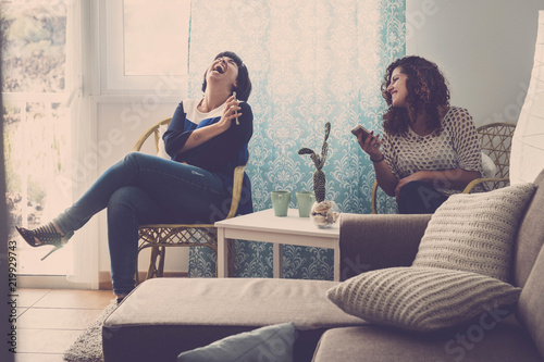 two young happy women friends sit down at home and laugh telling