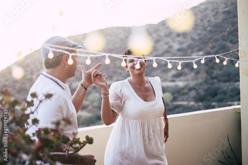 Fotografia  happy caucasian people dancing together at home in terrace with lights during the sunset