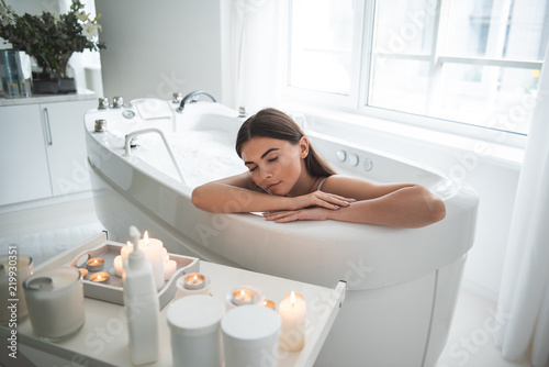 Photo Portrait of calm girl with closing eyes having leisure in water with foam opposi