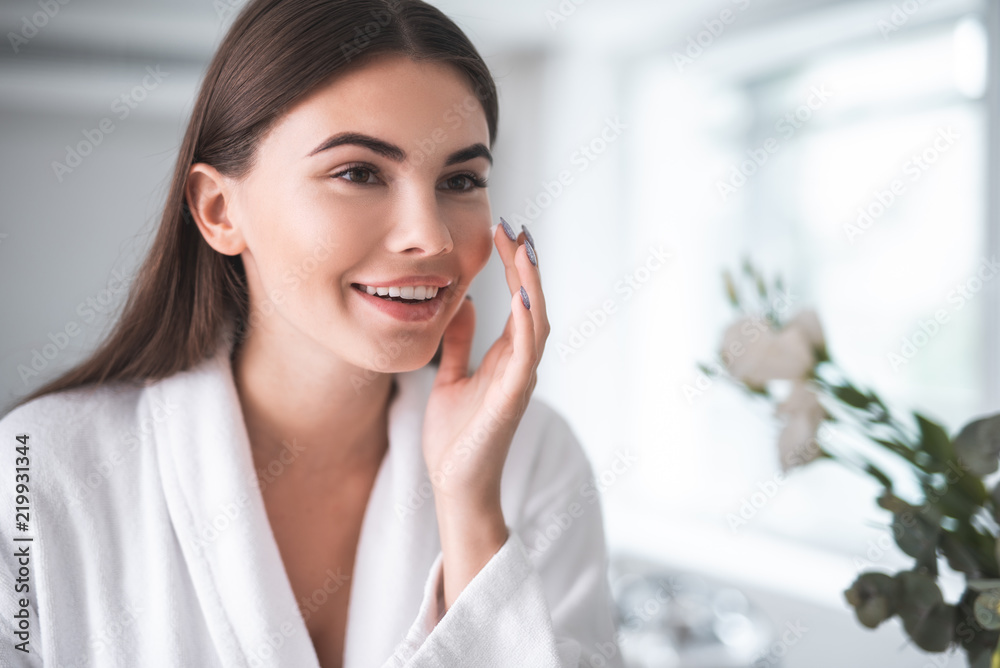 Fototapeta Portrait of pleased young lady touching cheek with hand. She putting cream on face skin indoor