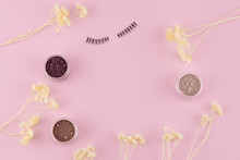 Glitter Eye Shadow Set And Fake Eyelashes Decorate With White Dried Flowers On Pastel Pink Background With Copy Space