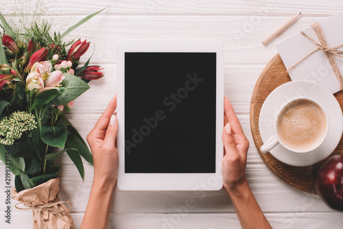 Fotografia  partial view of woman holding tablet at surface with cup of coffee and bouquet o