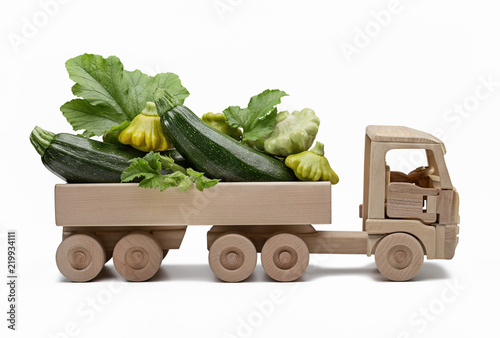 Truck, wooden toy for children, carries zucchini and pattypan squash.