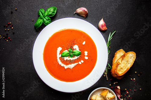 Tomato Soup with herbs on black slate table. Fresh homemade cream of Tomatoes soup with a swirl of cream. Top view.