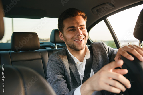 Smiling young business man passenger showing taxi driver