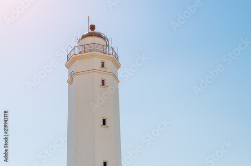 Foto op Canvas Vuurtoren White lighthouse against the blue sky on a sunny day