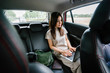 Portrait of a young Japanese woman getting some work done on her laptop while inside the car. She is being driven to her destination in a ride she booked on a ride hailing app.