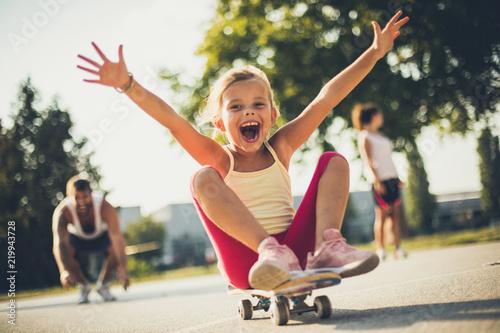Little girl on skateboard . Parents behind. Fototapete