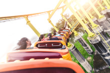 The Abstract Image Of The Roller Coaster Running On The Rail In Amusement Park. The Concept Of Extreme, Fun, Holiday And Vacation.