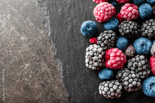 Obraz Slate plate with delicious frozen berries on grey background - fototapety do salonu