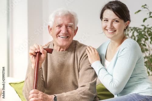 Fotografía  Smiling woman hugging happy senior man with walking stick during family meeting