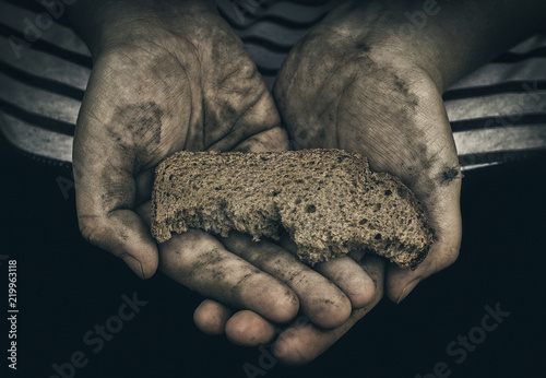 Foto Dirty hands of homeless poor man with piece of bread