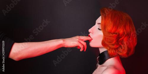 Photographie  Kinky redhead girl with bondage suck finger on black background