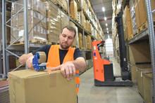 Verpacken Von Waren In Einen Karton Im Warenlager Durch Arbeiter - Im Hintergrund Interieur Hochregal Und Gabelstapler