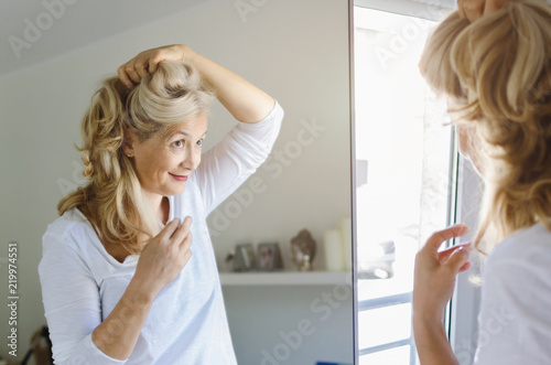 Foto  Woman cheking her hair in front of mirror