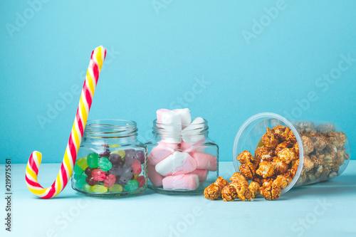Obraz na plátně  Sweet, caramelized popcorn, marshmallow and colorful lollipops in jars on a blue background