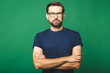 canvas print picture - A portrait of young handsome man in casual isolated on green background with glasses.