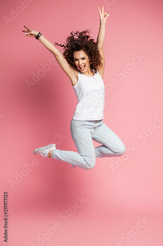Canvas Print Full length portrait of a joyful young woman jumping and celebrating over pink background