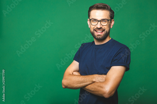 Fototapeta A portrait of young handsome man in casual isolated on green background with glasses. obraz