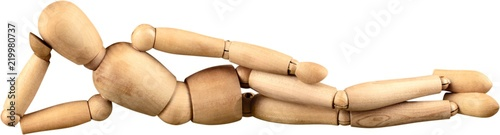 Obraz Miniature wooden mannequin in a laying down pose - fototapety do salonu