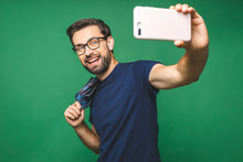 I Love Selfie! Handsome Young Man In Shirt Holding Camera And Making Selfie And Smiling While Standing Against Green Background.