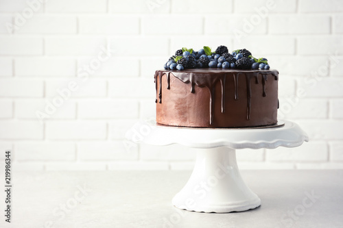 Fresh delicious homemade chocolate cake with berries on table against brick wall. Space for text