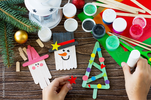 Fotografia The child glues the parts Christmas decoration or Christmas gift - Snowman, fir-tree and Santa