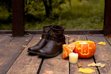 Autumn Shoes Next To A Halloween Pumpkin On A Wooden Floor In The Autumn Park