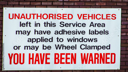 Fotografie, Obraz  Vehicle wheel clamping warning sign attached to a brick wall.