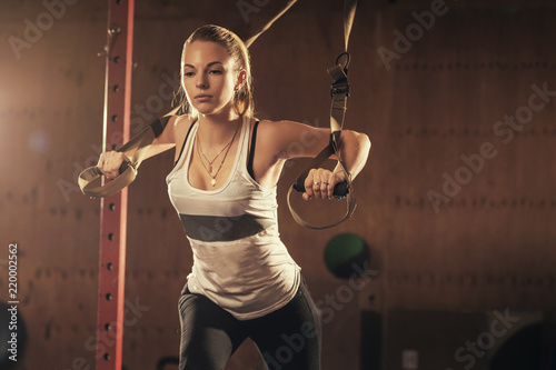 Fotomural  Woman athlete doing exercise in gym