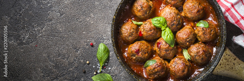 Fototapeta Meatballs in tomato sauce in a frying pan on dark stone table.  obraz