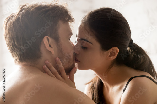 Fototapeta Close up of sensual young couple kissing in bedroom having romantic foreplay bef