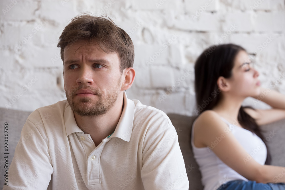 Fototapeta Upset millennial man think about relationship problems, having fight with proud female lover, offended couple not talking after family quarrel, sad male consider breaking up or divorce with girlfriend