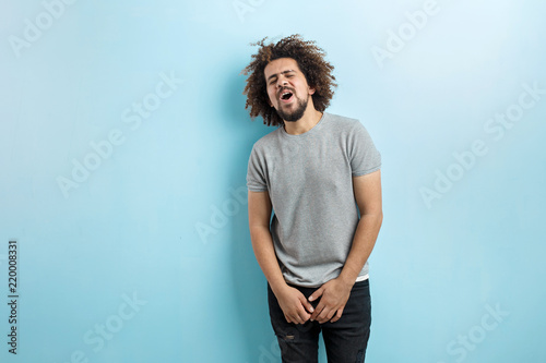 A curly-headed handsome man wearing a gray T-shirt is standing and laughing with his eyes closed over the blue background Fototapeta