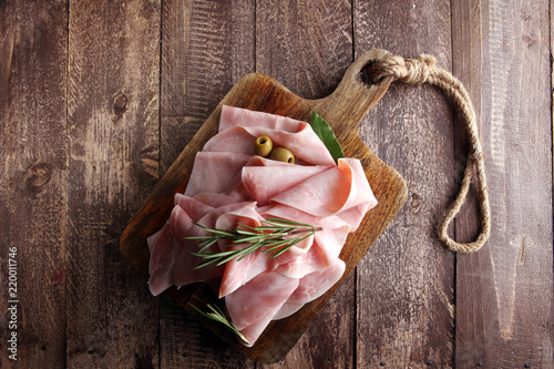 Sliced ham on wooden background. Fresh prosciutto. Pork ham sliced.