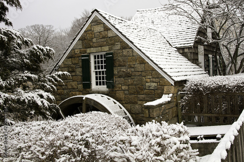 Photo  Restored old gristmill in snow showing water wheel