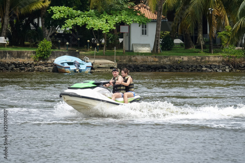Garden Poster Water Motor sports Happy young couple enjoying and having fun riding on a jet ski. Tropical coast of Sri Lanka