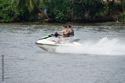 Garden Poster Water Motor sports Happy young couple enjoying and having fun riding on a jet ski. Tropical coast of Sri Lanka