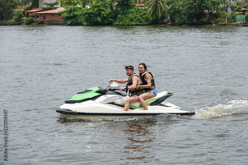La pose en embrasure Nautique motorise Happy young couple enjoying and having fun riding on a jet ski. Tropical coast of Sri Lanka