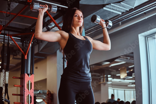 Foto  Blonde sportive female in sportswear doing exercise on shoulders with dumbbells in the fitness club or gym